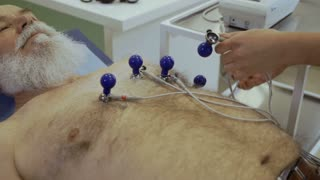 Doctor prepare old man to electrocardiography