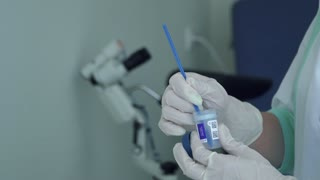 Doctor put sample of test into small container