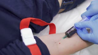 Doctor takes blood from vein