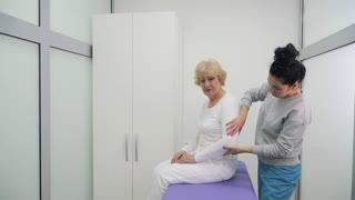 Doctor talks with elderly woman in clinic