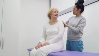 Doctor talks with senior woman in clinic