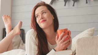 Dreamily red hair girl drinks a tea laying in bed in the photo studio