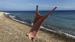 Dress dries on rope at sea background
