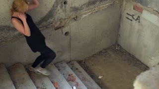 Drug addict descends the stairs in an abandoned building