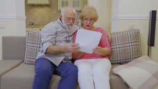 Elderly couple looks at the rent bills at home together