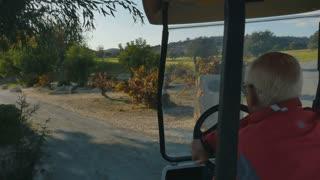 Elderly golfer drives the golf cart