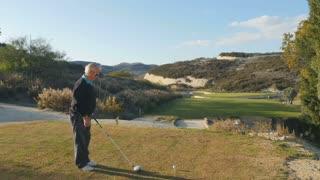 Elderly man wearing sunglasses play golf