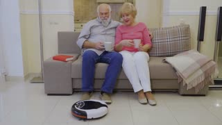 Elderly people relax on sofa at home during robot-vacuum cleaner clean floor