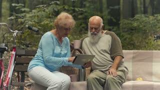 Elderly people with the tablet in the park