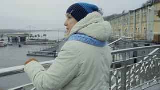 Elderly woman looks on the city from observation deck