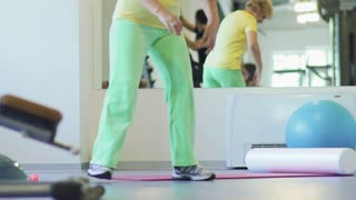 Elderly woman makes a sport exercise in the gym with sport equipment