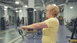 Elderly woman makes exercise for hands in the gym