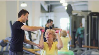 Elderly woman makes exercise with dumbbells in the gym with trainer