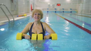 Elderly woman makes exercises with dumbbells in swimming pool