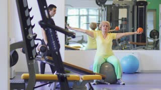Elderly woman makes fitness exercise with ball in the gym