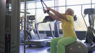 Elderly woman makes pull up exercise on training apparatus in the gym