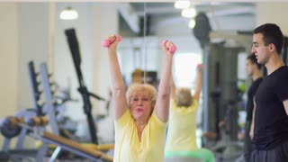 Elderly woman makes sport exercises with dumbbells in the gym