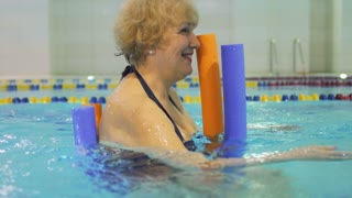 Elderly woman swims in pool