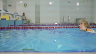 Elderly woman swims in swimming pool