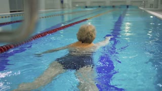 Elderly woman swims in the pool