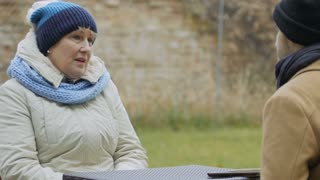 Elderly woman talks with man sitting in outdoors cafe