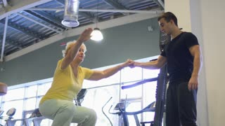 Elderly woman trains with coach in the gym