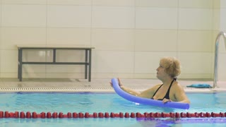 Elderly woman try to make exercise with noodle in swimming pool