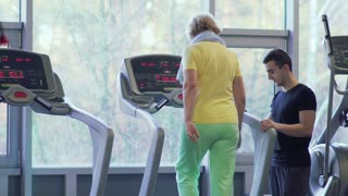 Elderly woman walks at the treadmill in the gym