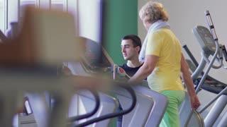 Elderly woman walks on treadmill in the gym