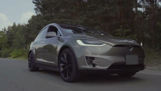Electric car riding near summer forest