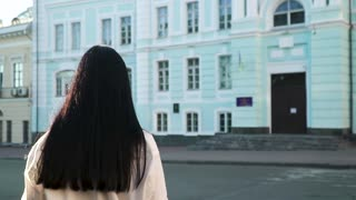 Elegance brunette with long hair moving to blue building in slow motion