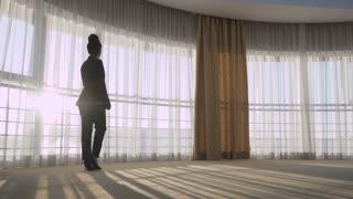 Elegance woman in black suit near panoramic windows