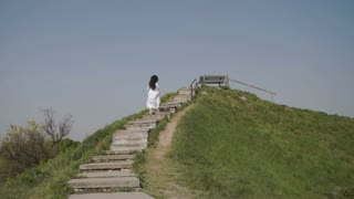 Elegance woman moves up the stairs on green hiil