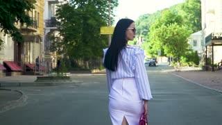 Elegant brunette in white skirt, stripped tunic and sunglasses walk in the city