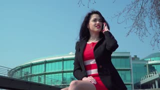 Elegant businesswoman in red dress talks by phone at business center background