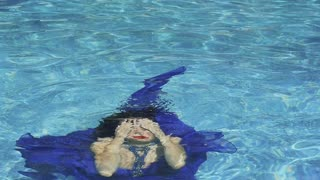 Elegant woman in blue dress emerges from water in swimming pool in slowmotion