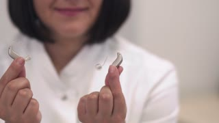 Employee of a medical clinic shows a hearing aid