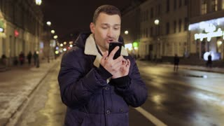 Expressive young man talks on phone at blurred city background
