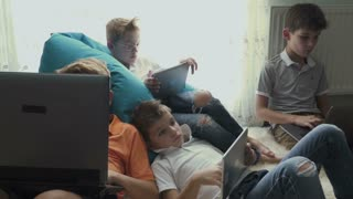 Family of brothers spend leisure time with electronic gadgets at home