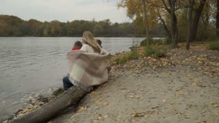 Family relax sitting on a log near river and enjoys a beautiful autumn landscape