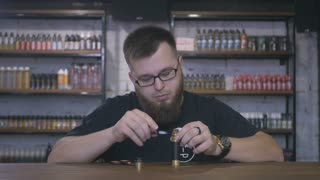 Fast shooting - salesman with beard complete the electronic cigarette in shop