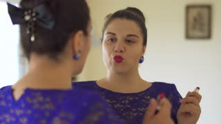 Fat girl paints her lips in front of a mirror