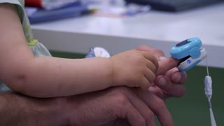 Father and little girl check the temperature of body at doctor's reception