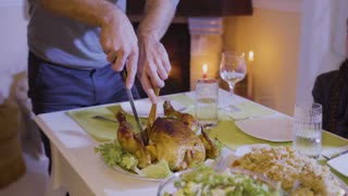 Father cuts a festive fried chicken at the christmas table