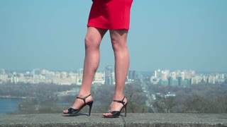 Female in red dress and in shoes on high heels walks at blurred city background