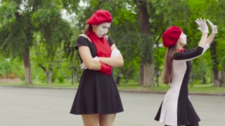 Female mimes play scenes in the park