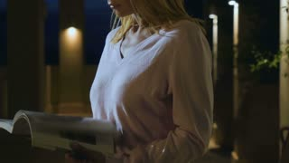 Female reads the journal under muffled light