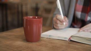 Female writes in notebook