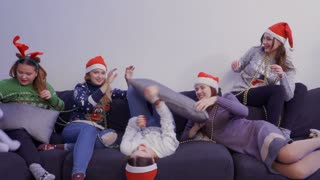 Five girls chilling on the sofa and play with each other