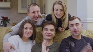 Five young caucasian people happily waves hands to camera